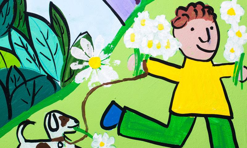 drawing of a boy running through some daisies with a dog