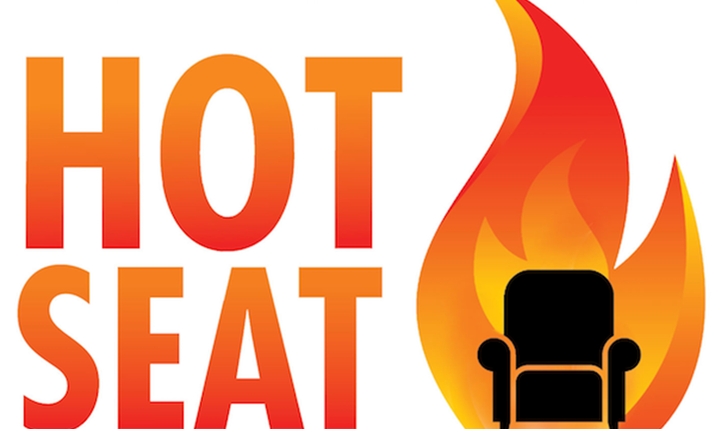 'HOT SEAT' text with a black chair next to it and behind the chair is a flame